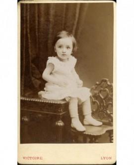 Petite fille assise sur une table