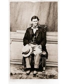 Homme en costume assis tenant un chapeau