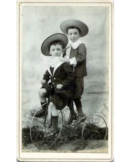 Deux enfants avec chapeau sur un tricycle (marinière)