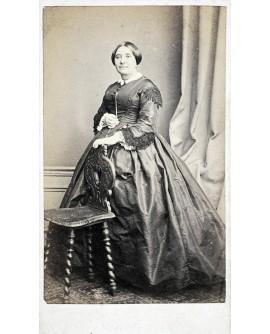 Femme en robe, main posée sur une chaise
