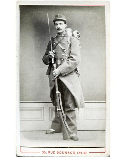 Militaire posant en grande tenue avec fusil et paquetage