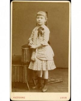 Petite fille accoudée à un fauteuil