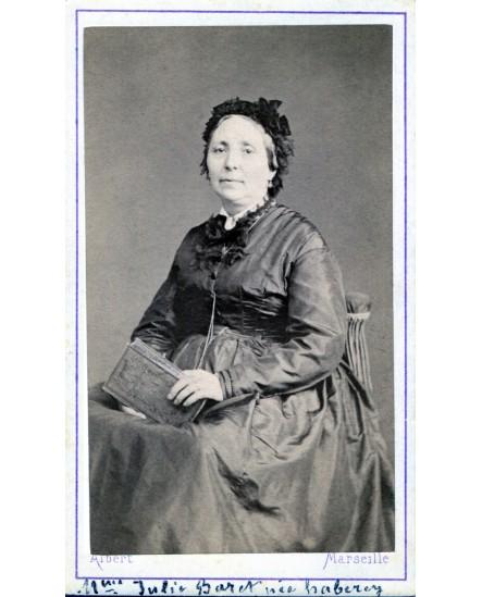 Femme posant assise tenant un livre. Julie Baret