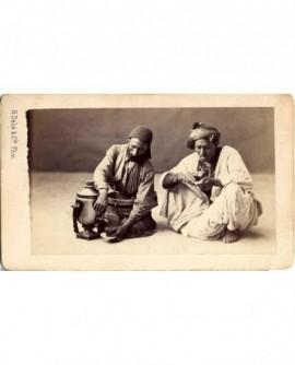 Arabes assis: vendeur et buveur de thé