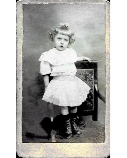 Fillette debout en robe sur une chaise