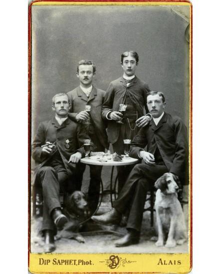 Quatre hommes atablés avec deux chiens