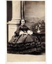 Jeune femme en grande robe posant assise