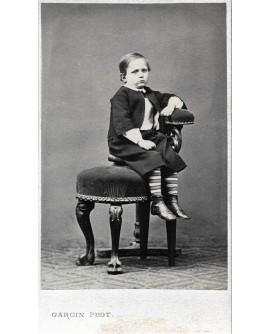 jeune garçon assis sur un tabouret