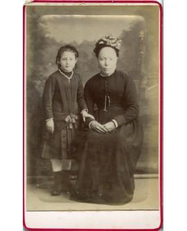 Femme en robe noire portant une charlotte à côté d'une jeune fille