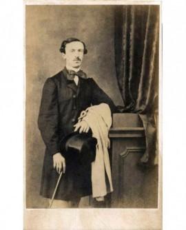 Homme moustachu debout, chapeau et canne à la main