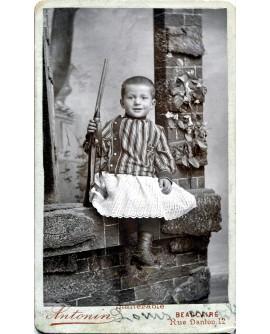 Jeune garçon assis tenant une carabine