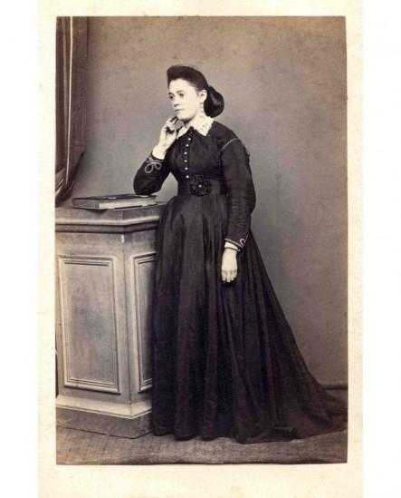 Jeuen fille en robe noire, accoudée sur un livre à fermoir