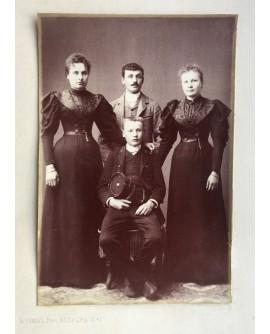 Jeune garçon en uniforme posant entre deux femme, un homme debout derrière lui