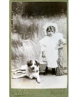 Fillette en robe et charlotte, avec un chien, tenant un saut