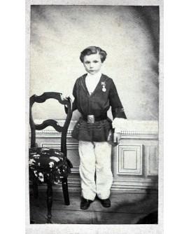 Jeune garçon tenant une chaise, médaille d'écolier