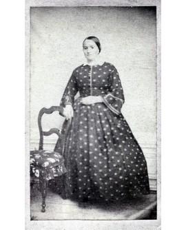 Femme en robe à pois appuyée à une chaise