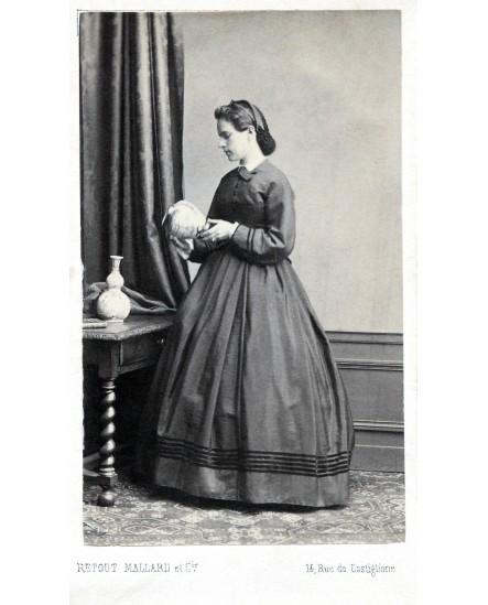 Femme debout en robe regardant une poterie