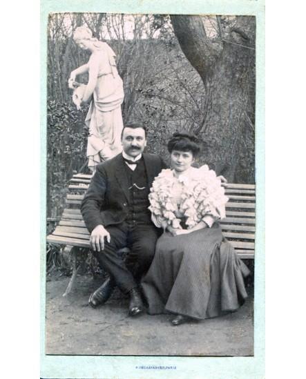 Couple posant assis dans un parc devant une statue