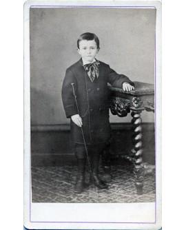 Jeune garçon debout tenant une cravache
