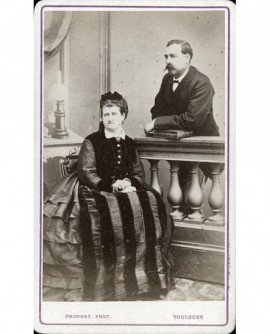femme en chapeau assise et homme moustachu debout derrière une balustrade