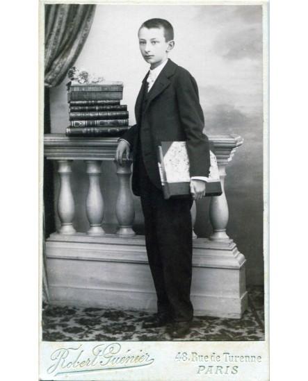 Jeune homme posant à coté de livres
