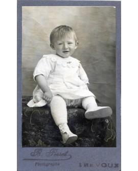 Jeune garçon posant assis