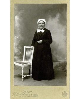 Femme en robe noire appuyée à une chaise