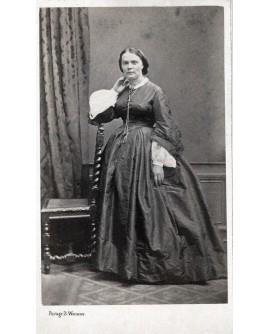 Mme Gérin. Femme en robe accoudée à une chaise
