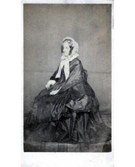 Femme âgée en grande robe et chapeau