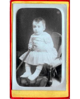Jeune enfant assis tenant une canne