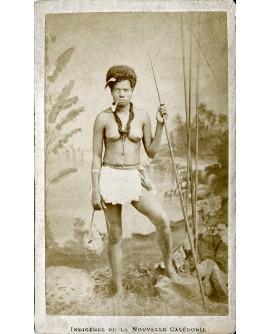 Femme indigène de Nouvelle Calédonie tenant une lance et fumant la pipe