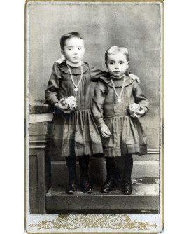 Couple d'enfants en robe portant une médaille