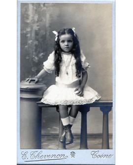 Fillette avec noeuds dans les cheveux, assise. Geneviève. 1908