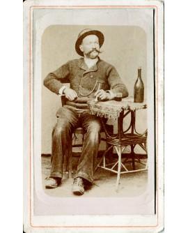Homme en chapeau assis avec une bouteille et un verre