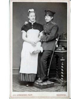 Jeune femme déguisée en militaire posant avec une domestique