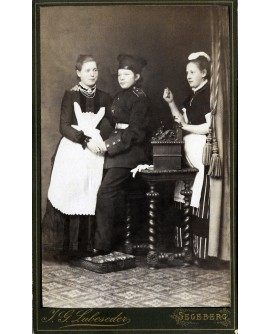 Jeune femme déguisée en militaire posant avec deux domestiques