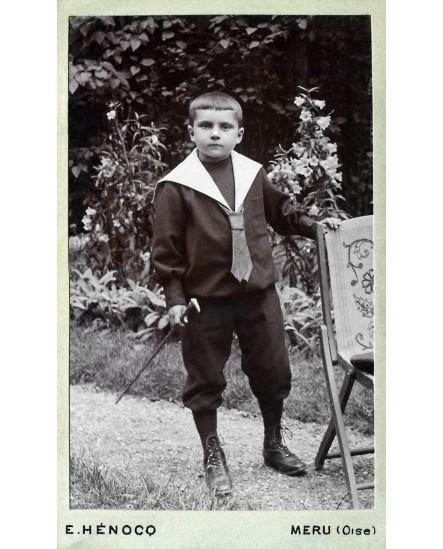 Jeune garçon en veste de marin tenant une canne