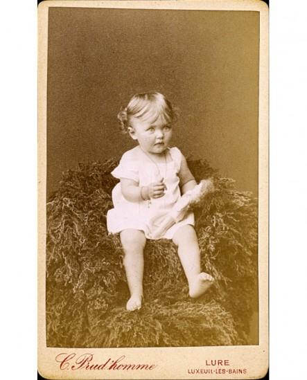 Bébé en chemise tenant sa poupée, assis sur une peau de mouton