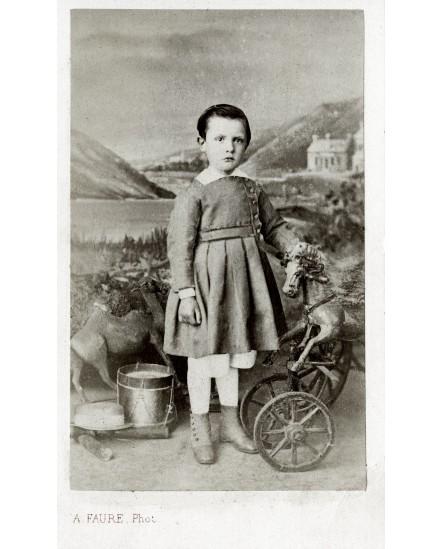 Jeune garçon entre un tambour et un cheval à roulette. jouet