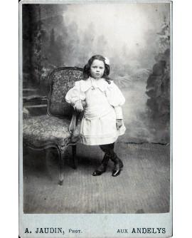 Fillette en robe accoudée à un fauteuil