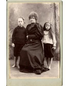 Femme posant entourée de deux enfants pieds nus