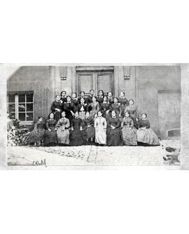 Groupe de femmes posant devant une maison