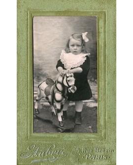 Fillette en robe à jabot avec un cheval de bois (jouet)