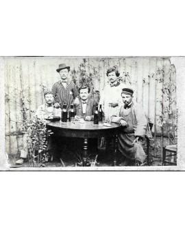 Cinq hommes assis buvant du vin