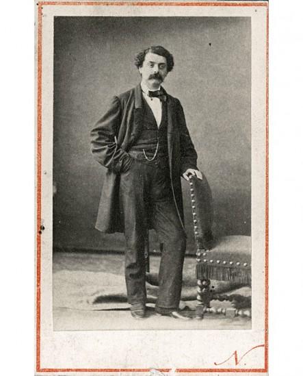 Homme moustachu debout, appuyé à une chaise, main dans la poche