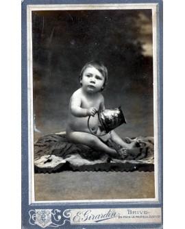 Bébé assis tenant un seau. jouet