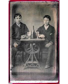 Deux hommes assis devant une bouteille et deux verres