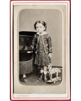 Fillette posant avec un cheval à roulette. jouet