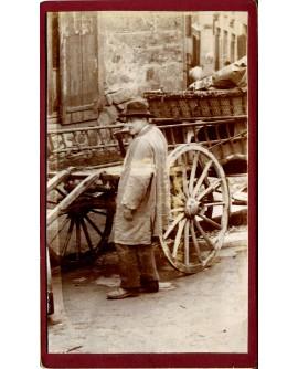 Homme en blouse devant une charrette