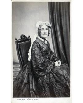 Femme âgée assise avec belle robe
